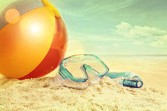 Beach ball and goggles in the sand Stock Photo