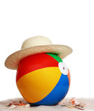 Beach ball and hat on beach sand Royalty Free Stock Images