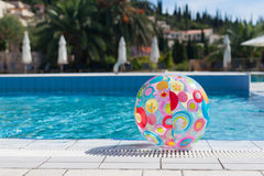 Beach ball by the pool Stock Images