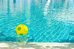 Beach Ball in Pool with sun reflection Stock Photos