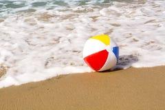 Beach ball on sand Stock Photography