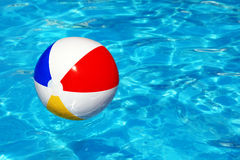 Beach ball in swimming pool. Beach ball floating in swimming pool abstract concept for summer vacations, relaxation and fun in the sunshine Stock Photo