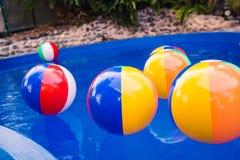 Beach ball variopinti che galleggiano nello stagno Immagini Stock