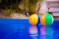 Beach ball variopinti che galleggiano nello stagno Fotografia Stock Libera da Diritti