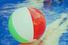 Beach ball variopinti che galleggiano nello stagno Immagini Stock Libere da Diritti