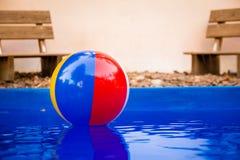 Beach ball variopinto che galleggia nello stagno Immagini Stock
