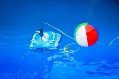 Beach ball variopinto che galleggia nello stagno ed accanto lui underwater un robot di pulizia Immagine Stock