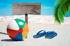 Beach Ball and wooden Signboard. Colorful Beach Ball, Flip Flops and a wooden Signboard on the Beach royalty free stock photos