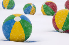 Beach Balls in Winter Snow. Beach Ballls during a winter snow storm.  Change of Seasons Royalty Free Stock Photo