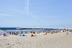 Beach at the Baltic sea at summer day, Kolobrzeg. KOLOBRZEG, POLAND - JULY 15, 2015: Unidentified sunbathers enjoys the sunshine on the wide for about 100 meters Royalty Free Stock Image