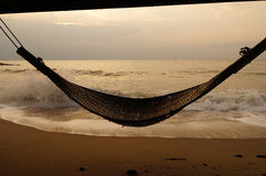 Beach bamboo cradle hanging by the sea in sunrise Royalty Free Stock Photography