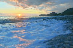 Beach of Bar city at sunset,Montenegro. Evening seascape with surf and sea foam in summer royalty free stock images