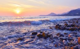 Beach of Bar city at sunset,Montenegro. Evening seascape with transparent wave in summer stock photo