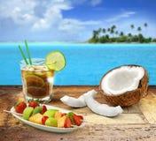 Beach bar menu. Cuba libre and tropical fruit on a wooden table in a polynesian seascape Stock Photography