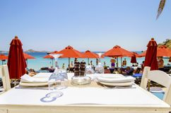 Beach bar restaurant, Mykonos. A table set with plates, glasses and napkins on a beach bar restaurant and a view of the sun umbrellas and the blue sea in Mykonos royalty free stock image