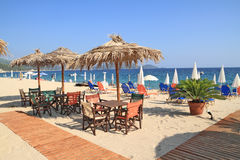 Beach bar by the sea. Beach bar with straw umbrellas and wooden deck on exotic resort Stock Photography