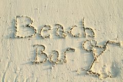 'Beach Bar' written in sand. Stock Photo