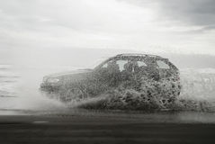 Sport Utility on beach with spray. Silhouette of modern all terrain vehicle driving fast on beach through water and making spray Stock Images