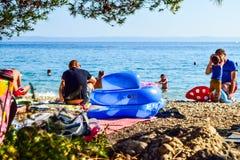 Beach in Baska Polje, Croatia. Baska Pole, Croatia - July 12, 2018: Vacationers on the public beach Baska Pole royalty free stock photos