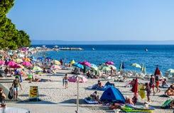 Beach in Baska Voda, Croatia. Baska Voda, Croatia - July 12, 2018: Vacationers on the public beach of Baska Voda stock photos