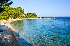 Beach in Baska Voda, Croatia. Baska Voda, Croatia - July 12, 2018: Vacationers on the public beach of Baska Voda stock image