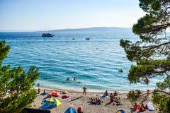 Beach in Baska Voda, Croatia. Baska Voda, Croatia - July 12, 2018: Vacationers on the public beach of Baska Voda royalty free stock image