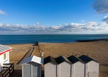 Beach bathing houses beach changing booths / beach huts, rocky beach and sea against blue sky and clouds. royalty free stock photos