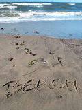 Beach on the beach with ocean. Word beach written on the sand with ocean in the background Royalty Free Stock Image
