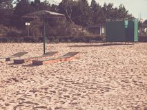 Beach. Three beds under the umbrella. Green dressing room on the backdrop of the cottage stock images