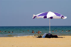 Beach and beach umbrella. A view of a group of people swimming at a beach in Turkey on a hot, sunny day with a large white and purple beach umbrella in the Royalty Free Stock Photo