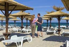 Beach ,beach umbrellas and young couple Stock Photos