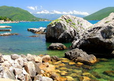 Beach with beautiful, picturesque rocks in the sea and mountains in the distance. Royalty Free Stock Images