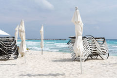 Beach, beautiful weather, sun loungers and umbrellas waiting for tourists in Cancun, Mexico. Stock Image