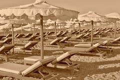 Beach beds and umbrellas closeup Stock Images