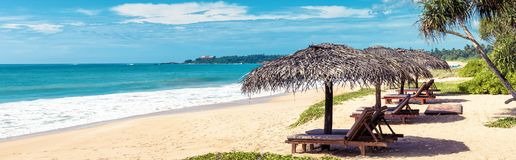 Beach beds with umbrellas on the tropical beach. Horizontal bunner for website header. Panoramic scenic view of a sand sunny beach in tropic. Beautiful sea Royalty Free Stock Photo