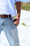 Beach Beer. Beer bottle in man's hand at beach stock images