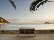 Beach with a Bench. Seascape of a beach on the Costa Blanca of Spain, with the famous Rock of Ifach on the background and a bench in the foreground Stock Images