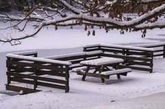 Beach Bench and Branches in Snow. Snow on wood picnic bench under tree beside pond at Clear Creek State Park, Pennsylvania Stock Photos