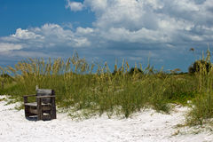 Beach, Bench and Sand Dune. Bench for Relaxation and White Sand Dune Against Green Vegetation and a Blue Cloudy Sky at Honeymoon Island in Florida Stock Images