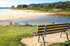 Beach bench. Slatted timber bench with outlook to creek, beach and ocean Stock Photography