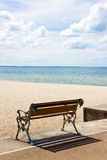 Beach and bench in sunny day Stock Photos