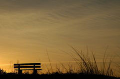 Beach bench at sunset. Beach bench on dunes, silhouetted at sunset Stock Image