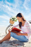 Beach bicycle woman reading book Stock Image