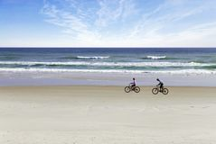Beach bikers. A couple relax as they bike up a pristine beach Stock Images