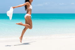 Beach bikini body - slim legs woman jumping. Beach ready bikini body - slim legs and toned thighs and butt. Suntan happy woman jumping in freedom on white sand stock photos