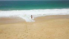 Beach bikini woman carefree running to the water on the beach. Picturesque ocean coast of Portugal stock video footage