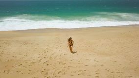 Beach bikini woman carefree running from the water on the beach. Picturesque ocean coast of Portugal stock footage