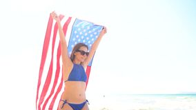 Beach bikini woman with US flag carefree walking along the water on the beach. Concept of Independence Day USA. Beach bikini woman with US flag carefree walking stock video footage