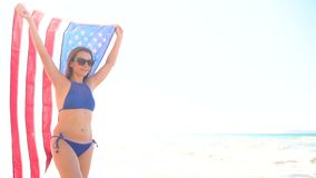 Beach bikini woman with US flag carefree walking along the water on the beach. Concept of Independence Day USA. Beach bikini woman with US flag carefree walking stock video