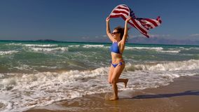 Beach bikini woman with US flag running along the water on the beach. Concept of Independence Day USA. Beach bikini woman with US flag running along the water on stock video
